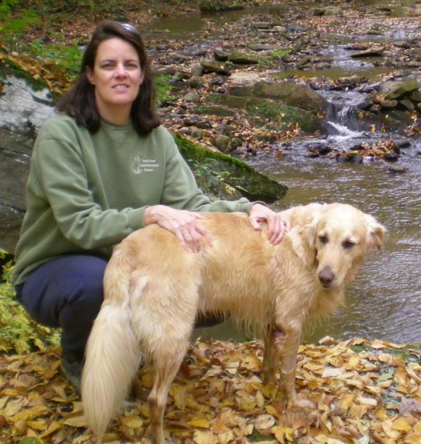 woman with dog by mountain creek