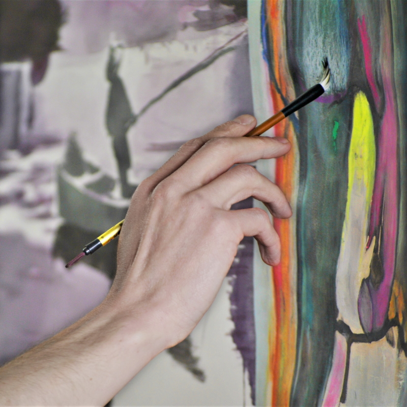 persons hand painting on a canvas